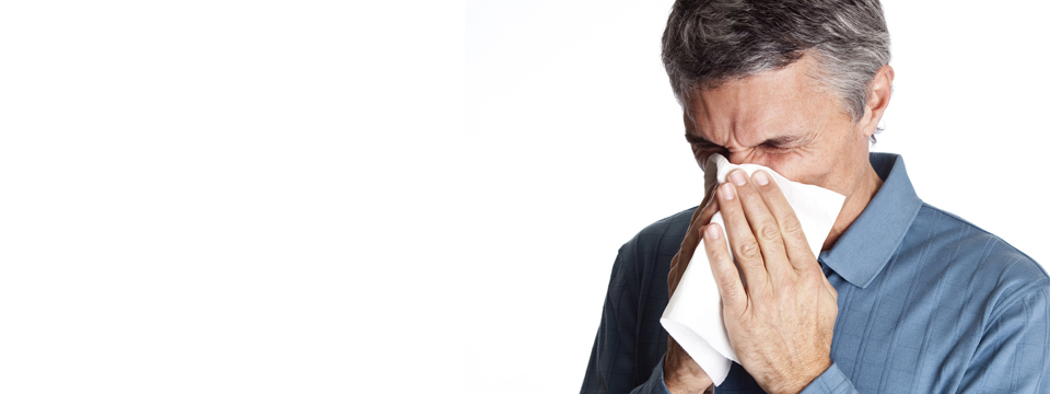Man sneezing into tissue covering nose and mouth